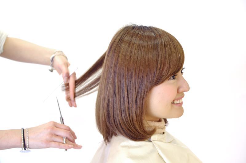 美容師さんに髪をきってもらう女性