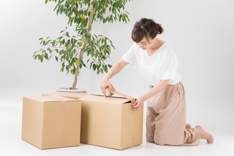引っ越しの荷物を箱詰めする人